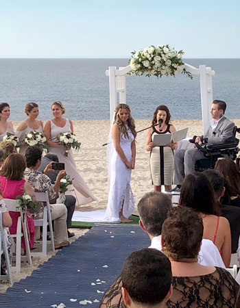 Wedding ceremony officiant Reverend Loriann performaing a wedding ceremony on a Long Island beach